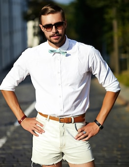 Handsome hipster model man in stylish summer clothes posing in sunglasses