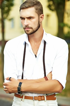 Handsome hipster model man in stylish summer clothes posing