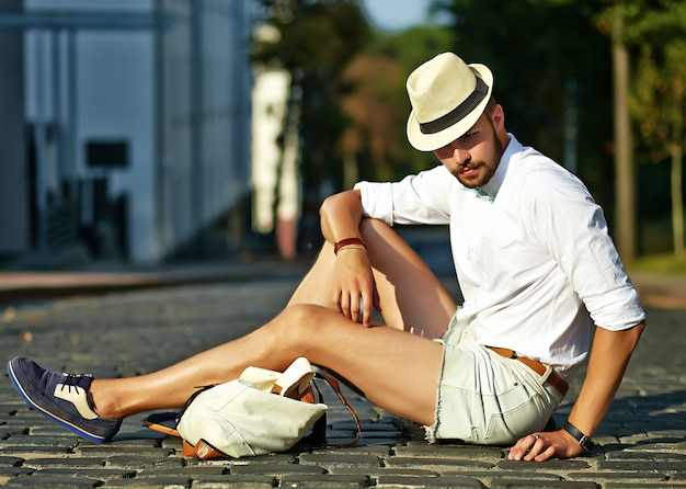 Handsome hipster model man in stylish summer clothes sitting  in hat with bag