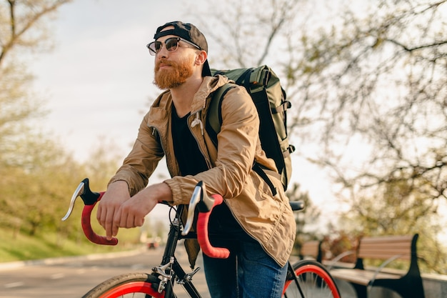 Красивый бородатый мужчина в стиле хипстера в куртке и солнцезащитных очках, едущий в одиночестве с рюкзаком на велосипеде, здоровый активный образ жизни, путешественник с рюкзаком