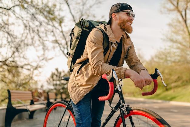 自転車の健康的なアクティブなライフスタイルの旅行者のバックパッカーにバックパックと一緒に一人で乗っているジャケットとサングラスのハンサムなヒップスタースタイルのひげを生やした男