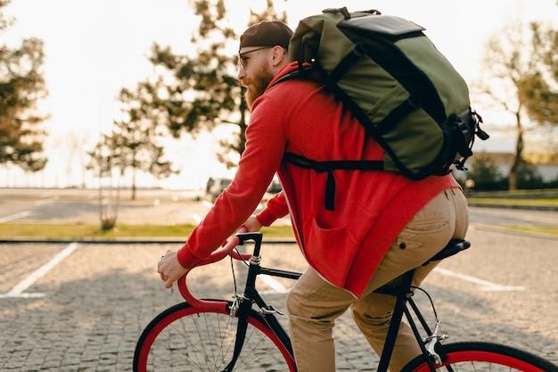 赤いパーカーとサングラスのハンサムなヒップスタースタイルのひげを生やした男は、自転車の健康的なアクティブなライフスタイルの旅行者のバックパッカーにバックパックと一緒に乗っています