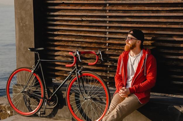 海の健康的なアクティブなライフスタイルの旅行者のバックパッカーによって朝日の出にバックパックと自転車で一人でリラックスして座っている赤いパーカーのハンサムなヒップスタースタイルのひげを生やした男
