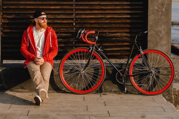 Uomo barbuto bello stile hipster in felpa con cappuccio rossa seduto rilassante da solo con zaino e bicicletta all'alba di mattina in riva al mare viaggiatore zaino in spalla sano stile di vita attivo