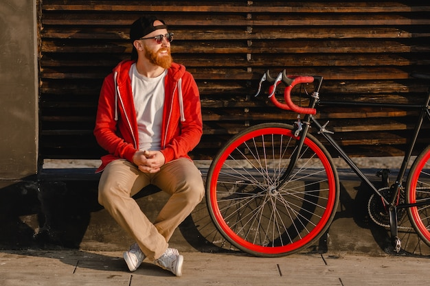 Handsome hipster style bearded man in red hoodie sitting relaxing alone with backpack and bicycle in morning sunrise by the sea healthy active lifestyle traveler backpacker