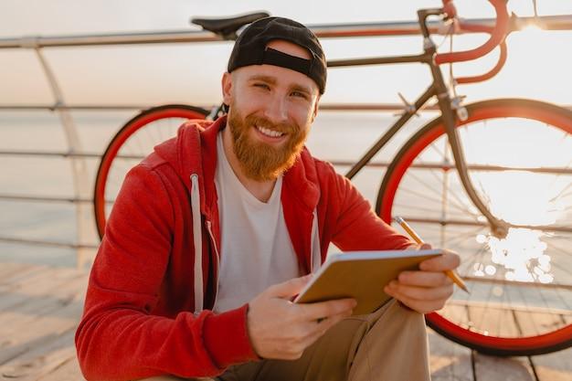 Uomo barbuto bello stile hipster in felpa con cappuccio rossa che studia scrittura freelance online prendendo appunti con la bicicletta all'alba di mattina in riva al mare sano stile di vita attivo