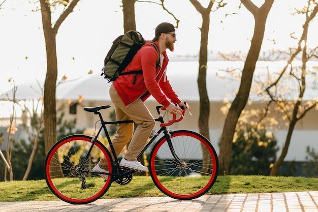 Uomo barbuto bello stile hipster in felpa con cappuccio rossa e occhiali da sole in sella da solo con lo zaino in bicicletta viaggiatore zaino in spalla sano stile di vita attivo