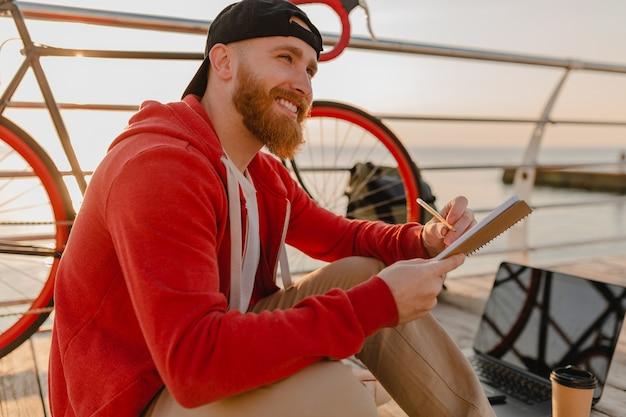 海の健康的なアクティブなライフスタイルの旅行者のバックパッカーによる朝の日の出でバックパックと自転車でメモを書くオンラインフリーランサーを勉強しているハンサムなヒップスタースタイルのひげを生やした男