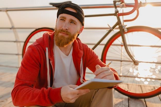 Uomo barbuto bello stile hipster che pensa in felpa con cappuccio rossa studiando scrittura freelance online prendendo appunti con la bicicletta all'alba di mattina in riva al mare sano stile di vita attivo