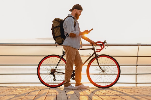 Handsome hipster style bearded man traveling with backpack on bicycle using phone in morning sunrise by the sea, healthy active lifestyle