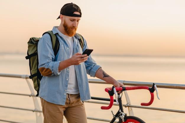 Uomo barbuto bello stile hipster utilizzando il telefono in viaggio con zaino e bicicletta all'alba in riva al mare, viaggiatore con zaino e sacco a pelo sano stile di vita attivo