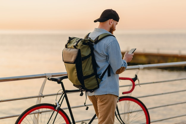 Handsome hipster style bearded man using phone traveling with backpack and bicycle in morning sunrise by the sea, healthy active lifestyle traveler backpacker
