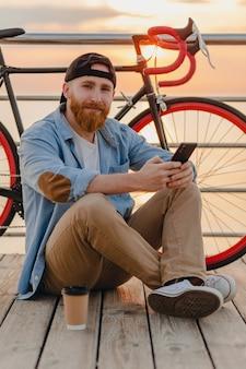 Красивый бородатый мужчина в стиле хипстера в джинсовой рубашке и кепке, держащий смартфон с велосипедом на утреннем восходе солнца у моря, пьет кофе, путешественник, ведущий здоровый активный образ жизни
