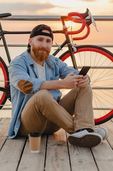 Handsome hipster style bearded man wearing denim shirt and cap holding smartphone with bicycle in morning sunrise by the sea drinking coffee, healthy active lifestyle traveler