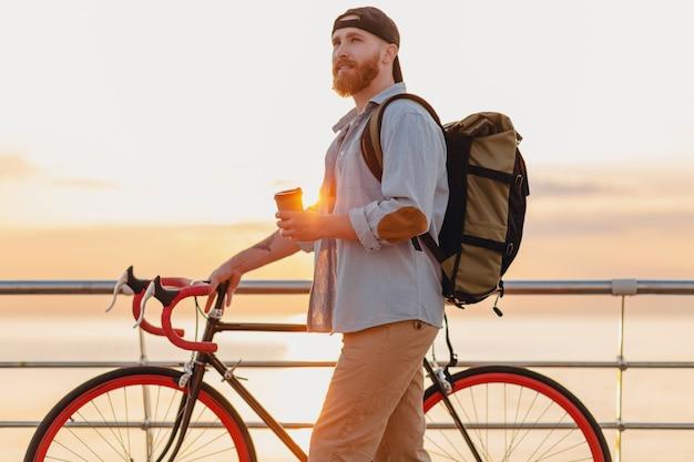 Красивый бородатый мужчина в стиле хипстера с рюкзаком в джинсовой рубашке и кепке с велосипедом на утреннем восходе солнца у моря, пьющий кофе, путешественник, путешествующий по здоровому активному образу жизни