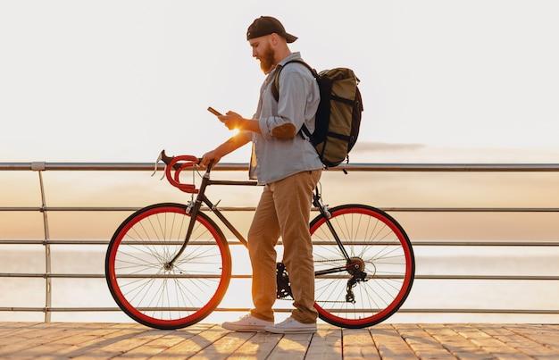 커피를 마시는 바다로 아침 일출에 자전거와 데님 셔츠와 모자를 착용하는 배낭, 건강한 활동적인 라이프 스타일 여행자 배낭을 가진 잘 생긴 힙 스터 스타일 수염 난 남자