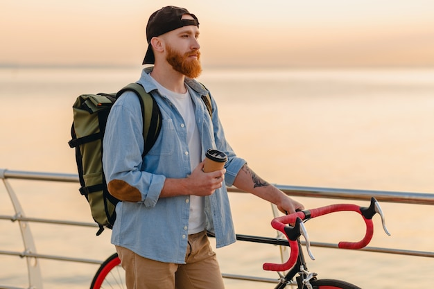 Handsome hipster style bearded man with backpack wearing denim shirt and cap with bicycle in morning sunrise by the sea drinking coffee, healthy active lifestyle traveler backpacker