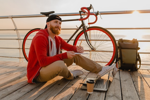 Handsome hipster style bearded man working online freelancer on laptop with backpack and bicycle in morning sunrise by the sea healthy active lifestyle traveler backpacker