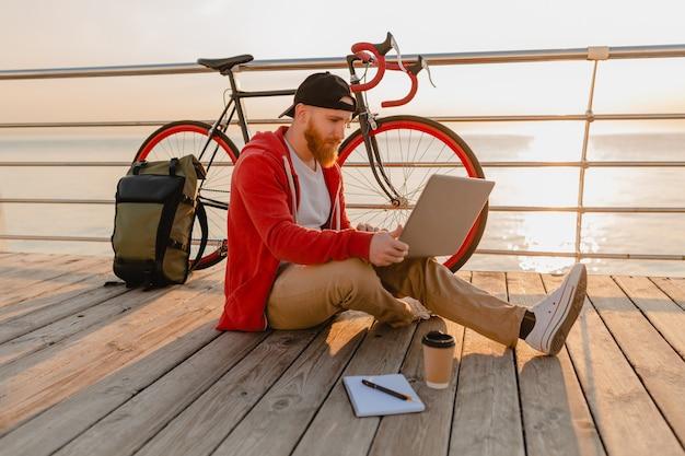 海の健康的なアクティブなライフスタイルの旅行者のバックパッカーによる朝の日の出でバックパックと自転車とラップトップでオンラインフリーランサーで働くハンサムなヒップスタースタイルのひげを生やした男