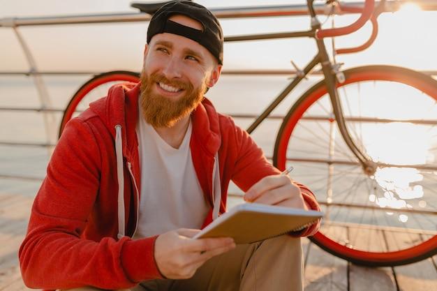 바다 건강한 활동적인 라이프 스타일 여행자 배낭에 의해 아침 일출에 배낭과 자전거 노트북에 온라인 프리랜서 작업 잘 생긴 힙 스터 스타일 수염 난된 남자
