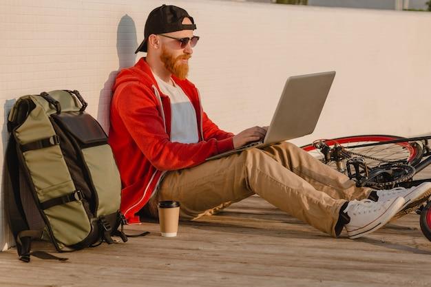 Красивый бородатый мужчина в стиле хипстера, работающий онлайн-фрилансером на ноутбуке с рюкзаком и велосипедом в утреннем восходе солнца у моря, здоровый активный образ жизни, путешественник с рюкзаком
