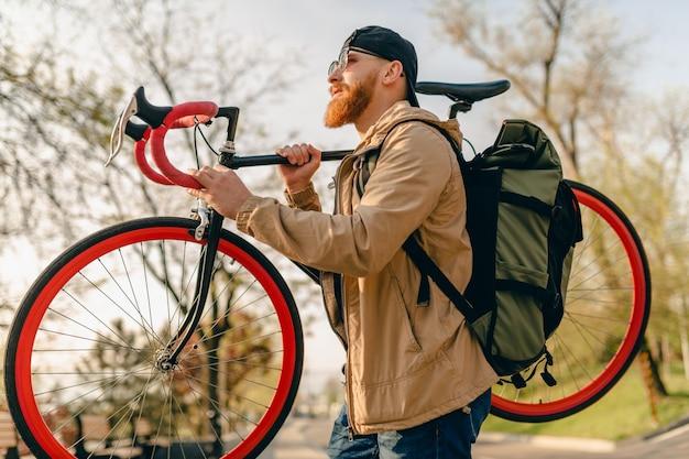 ハンサムな流行に敏感なスタイリッシュなひげを生やしたジャケットとサングラスの男が自転車でバックパックを持って通りを一人で歩く健康的なアクティブなライフスタイルの旅行者のバックパッカー
