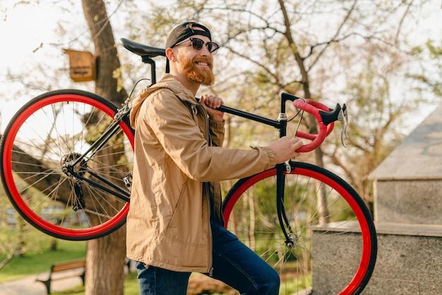 Uomo barbuto alla moda hipster bello in giacca e occhiali da sole che cammina da solo in strada con lo zaino in bicicletta viaggiatore zaino in spalla sano stile di vita attivo