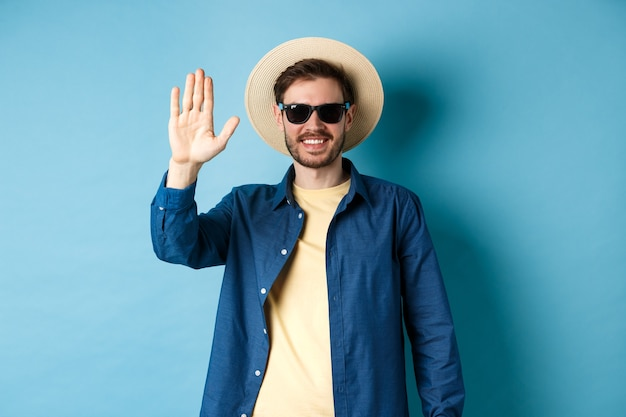 Handsome hipster on summer holiday, waiving hand and smiling, saying hello, wearing sunglasses and straw hat, blue background.