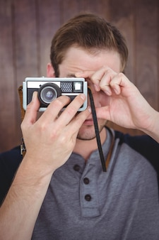 Handsome hipster taking picture with retro camera