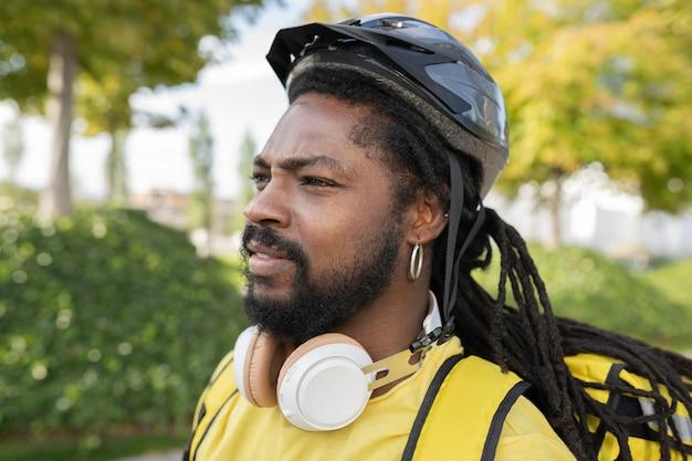 Красивый латиноамериканец с дредами и доставкой посылки с велосипедным шлемом