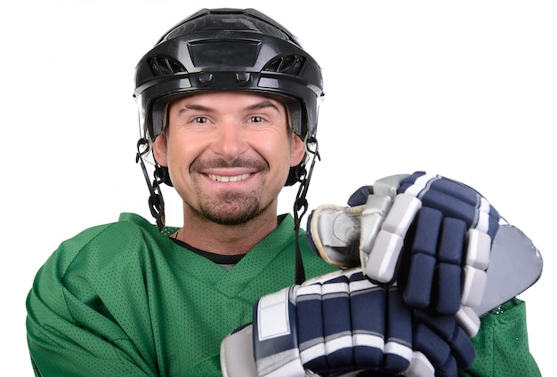Handsome hockey player is smiling at camera.