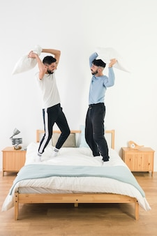 Handsome homosexual couple fighting with pillow on bed