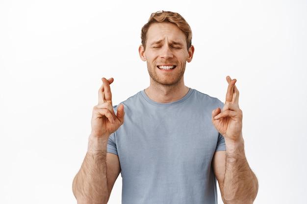 Красивый обнадеживающий рыжий парень молится, закрывает глаза и скрещивает пальцы на удачу, загадывает желание, ждет знака, ожидает новостей, стоит над белой стеной