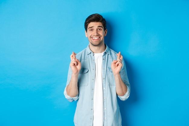 Красивый обнадеживающий мужчина загадывает желание, скрещивает пальцы и улыбается, ожидая результатов, стоя на синем фоне