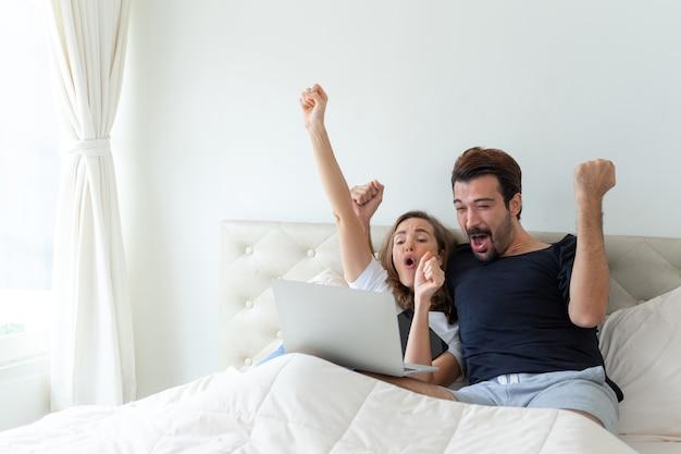 잘 생긴 남편과 아름다운 아내는 그들이 응원하는 축구가 침실에서 승자 챔피언 일 때 기분이 좋습니다.