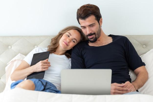 Красивый муж и красивая жена чувствуют себя романтической парой, смотрящей фильмы с портативного компьютера в спальне