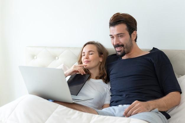 잘 생긴 남편과 아름다운 아내는 침대 방에서 컴퓨터 노트북에서 영화를 보는 낭만적 인 부부를 느낍니다.