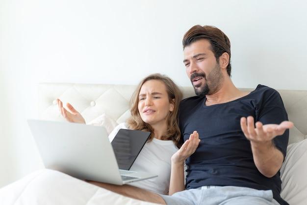 Bel marito e bella moglie si sentono coppia romantica guardando film dal computer portatile nella camera da letto