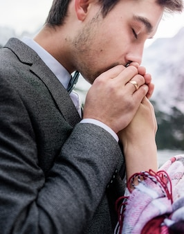 Handsome husbant is tenderly kissing wife's hands with closed eyes, happy marriage
