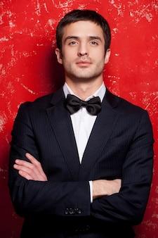 蝶ネクタイでハンサム。スーツと蝶ネクタイのハンサムな若い男は、腕を組んで、赤い背景に立っている間、カメラを見ています。