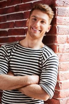 ストライプのシャツでハンサム。カメラを見て、レンガの壁に寄りかかって笑っている縞模様のシャツの陽気な若い男
