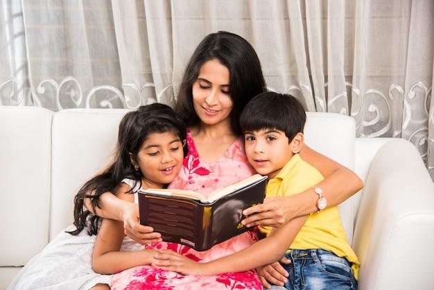 ハンサムなインドのアジアの父または家でソファの上に座っている間子供のための本を読んでいるかわいい母親