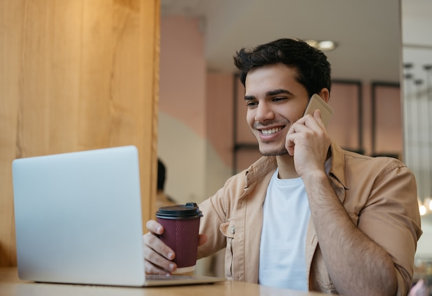 Handsome indian businessman talking on mobile phone, holding cup of coffee, working from home