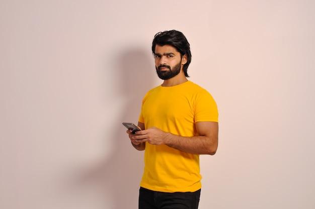핸드폰으로 메시지를 읽는 진지한 표정으로 카메라를 쳐다보는 티셔츠 차림의 잘생긴 인도 남자