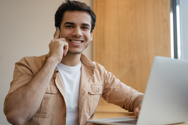 Handsome indian man using laptop talking on mobile phone working from home