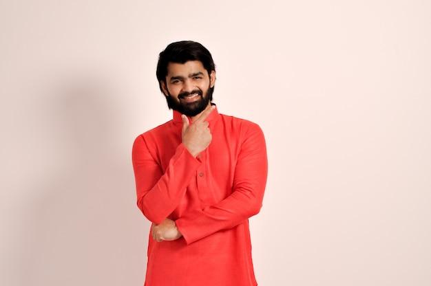 쿠르타를 입고 얼굴 근처에서 손가락으로 웃고 있는 잘생긴 인도 남자