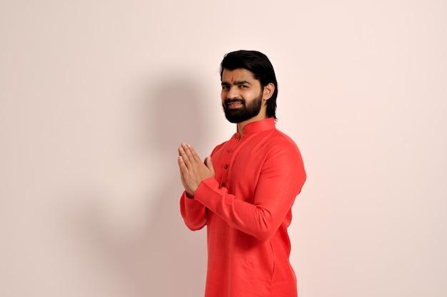 쿠르타를 입고 웃고 있는 잘생긴 인도 남자가 손으로 나마스테 제스처를 하고 있다.