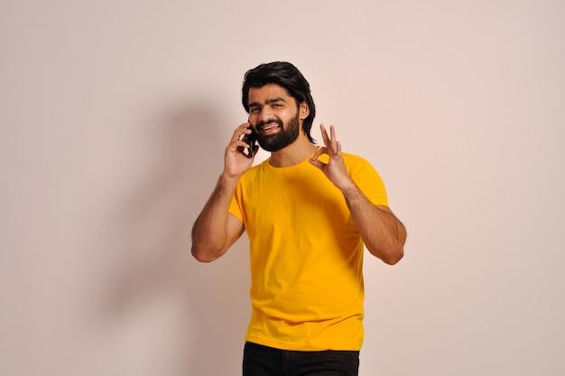 T셔츠를 입은 잘생긴 인도 남자 휴대 전화로 이야기하고 손으로 괜찮은 표시를 보여줍니다.