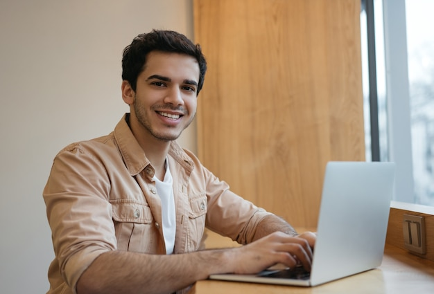 Handsome indian programmer using laptop computer working from home