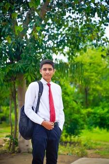 白いシャツと赤いネクタイを身に着けているハンサムなインドの少年